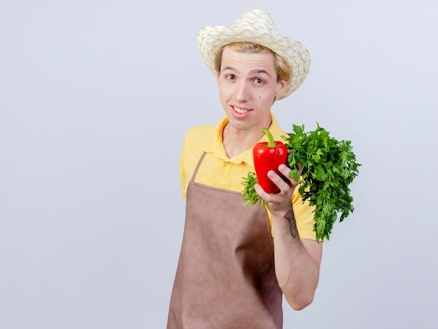 Młody ogrodnik ubrany w kombinezon i kapelusz, trzymający czerwoną paprykę i świeże zioła z uśmiechem na twarzy