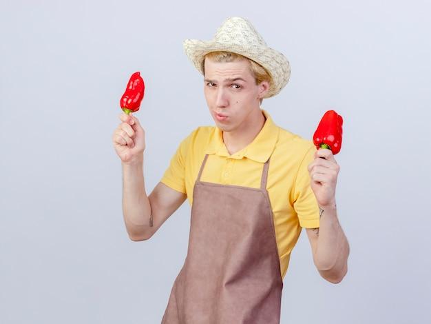 Młody ogrodnik ubrany w kombinezon i kapelusz, trzymający czerwoną paprykę ze sceptycznym uśmiechem