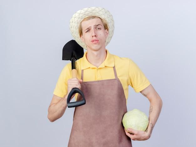 Młody ogrodnik ubrany w kombinezon i kapelusz, trzymający łopatę i kapustę, wyglądający pewnie