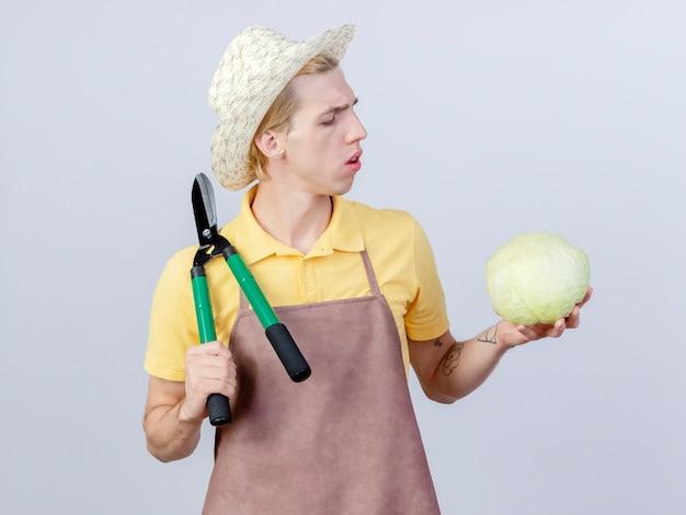 Młody ogrodnik ubrany w kombinezon i kapelusz, trzymający nożyce do żywopłotu, patrzący na kapustę w ręku, jest zaintrygowany