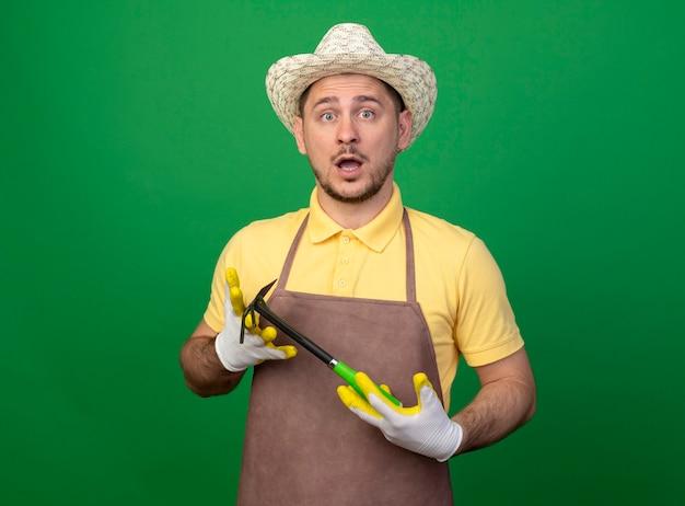 Młody ogrodnik w kombinezonie i kapeluszu w roboczych rękawiczkach demonstruje gratkę patrząc na przód zaskoczony stojąc nad zieloną ścianą