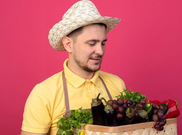 Młody ogrodnik w kombinezonie i kapeluszu w roboczych rękawiczkach, trzymając skrzynię pełną warzyw patrząc na nich uśmiechniętych stojących nad różową ścianą