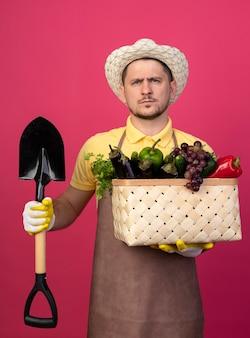 Młody ogrodnik w kombinezonie i kapeluszu w roboczych rękawiczkach trzymający skrzynię pełną warzyw z łopatą patrząc z przodu z poważną twarzą stojącą nad różową ścianą