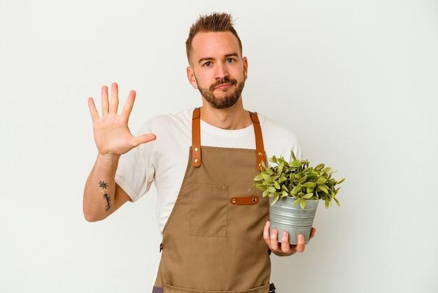Młody ogrodnik wytatuowany kaukaski mężczyzna trzyma roślinę na białym tle na białej ścianie uśmiechnięty wesoły pokazując numer pięć palcami.