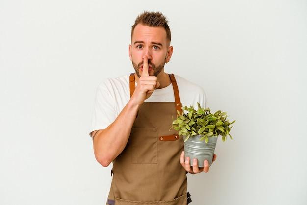 Młody ogrodnik wytatuowany kaukaski mężczyzna trzyma roślinę na białym tle na białej ścianie, zachowując tajemnicę lub prosząc o ciszę.