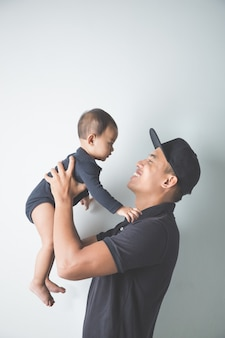 Młody ojciec azjatyckich, trzymając jego urocze dziecko