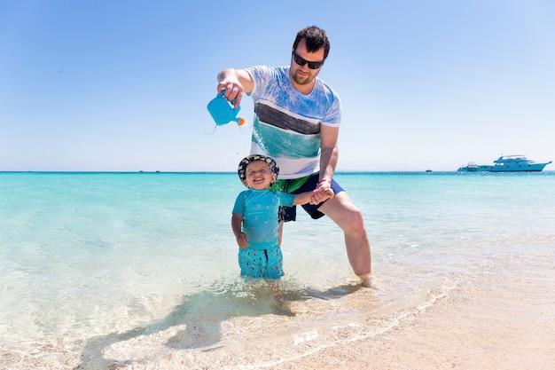 Młody ojciec bawi się na plaży ze swoim małym synkiem i podlewa go z konewki. mały chłopiec śmiejący się nad morzem.