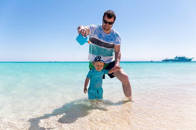 Młody ojciec bawi się na plaży ze swoim małym synkiem i podlewa go z konewki. mały chłopiec śmieje się nad morzem.