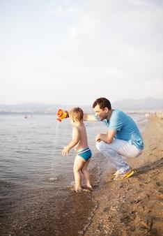 Młody ojciec bawić się z jego synem przy plażą
