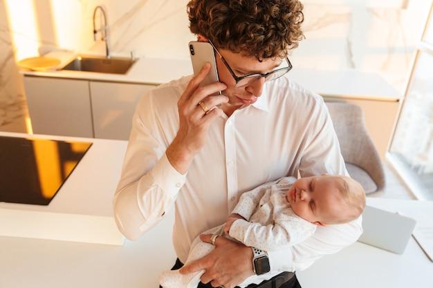 Młody ojciec biznesmen bawi się ze swoim małym synkiem podczas rozmowy przez telefon komórkowy w domu