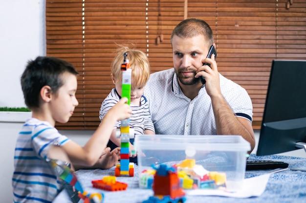 Młody ojciec biznesowego mężczyzny rodzic przeszkadza synom swoich dzieci podczas pracy w domu.