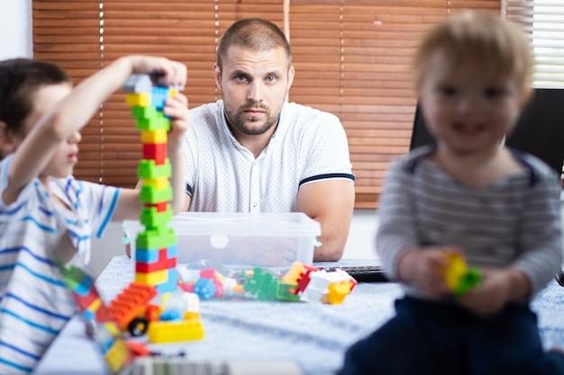 Młody ojciec biznesowy rodzic przerywa pracę w domu synom swoich dzieci.