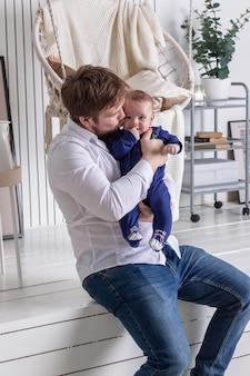 Młody ojciec całuje swoje małe dziecko w policzek w studio