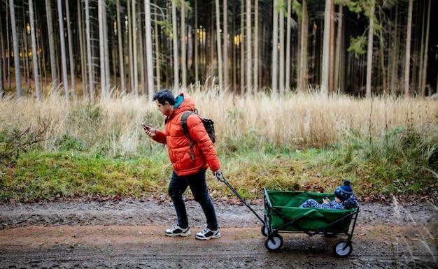 Młody ojciec chodzi z dzieckiem w wozie w lesie