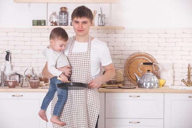 Młody ojciec gotuje ze swoim małym synkiem. tata i dziecko w kuchni. pomocnicy dnia matki. mężczyzna z dzieckiem robi obiad lub śniadanie dla matki.