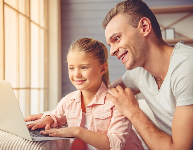 Młody ojciec i jego córeczka używają laptopa.