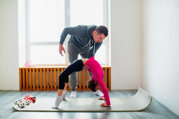 Młody ojciec i jego śliczna córeczka ćwiczą w domu w pozie brydża. słodkie dziecko i tata trenują na macie wewnątrz. noszą odzież sportową i ćwiczą w pobliżu okna w pokoju