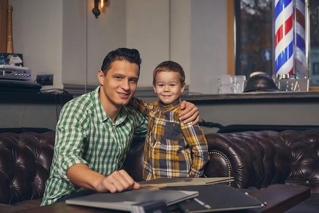 Młody ojciec i jego stylowy synek w zakładzie fryzjerskim w poczekalni