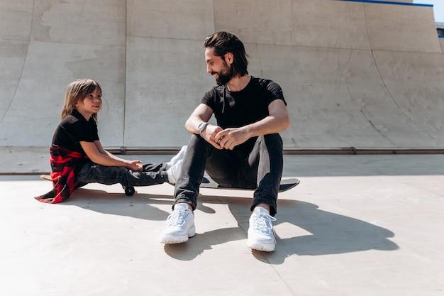 Młody ojciec i jego syn ubrani w zwykłe ubrania siedzą na deskorolkach w skateparku w słoneczny dzień.