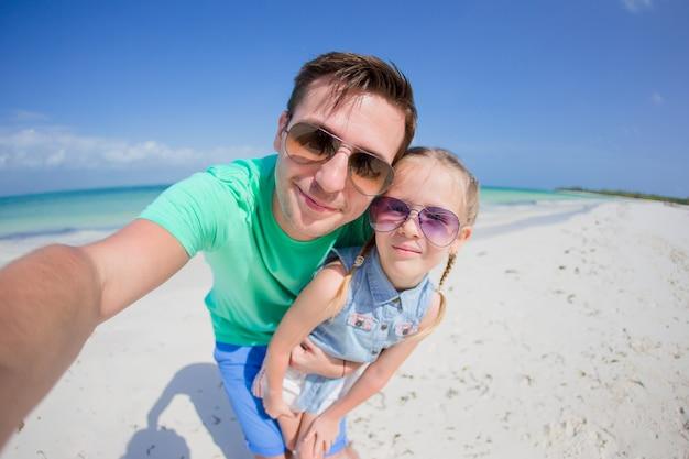 Młody ojciec i małe dziecko biorąc selfie zdjęcie na plaży