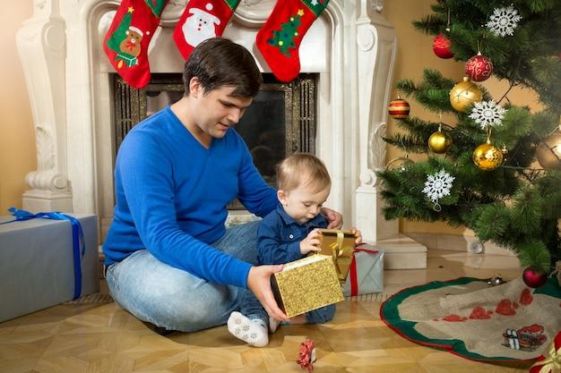 Młody ojciec i uroczy synek otwierają prezenty świąteczne na podłodze w salonie