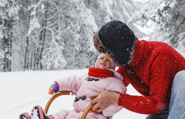 Młody ojciec jeździ na drewnianych saniach ze swoją uroczą córką po zaśnieżonym lesie. zabawy dla dzieci