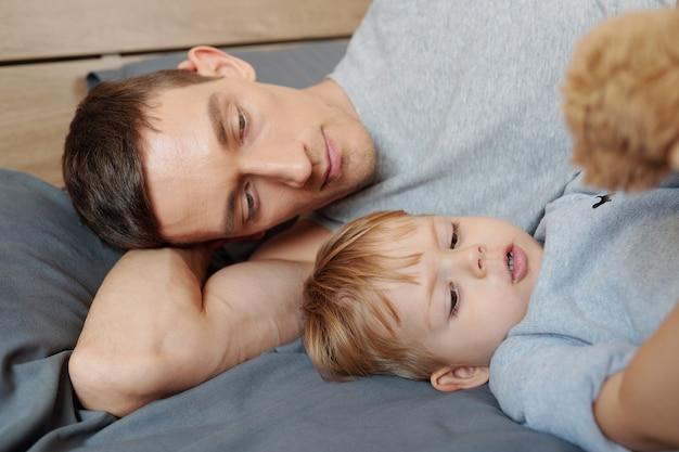 Młody ojciec leżący na łóżku i odpoczywający razem ze swoim małym synkiem podczas godziny snu