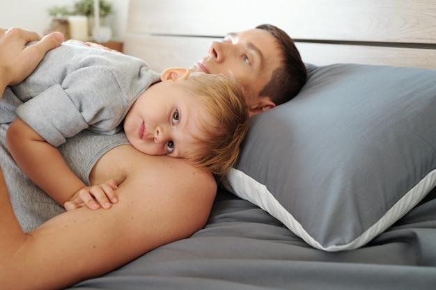 Młody ojciec leżący na łóżku razem ze swoim dzieckiem i usypiający go w godzinach snu