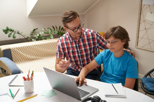 Młody ojciec noszący okulary, pomagający synowi w odrabianiu lekcji, chłopiec korzystający z laptopa