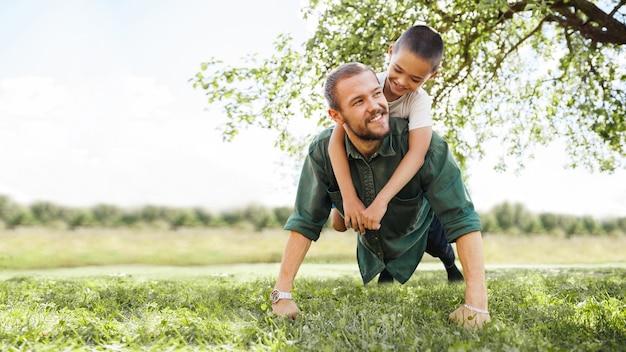 Młody ojciec robi pompki na ulicy z synem na plecach, wychowuje dzieci
