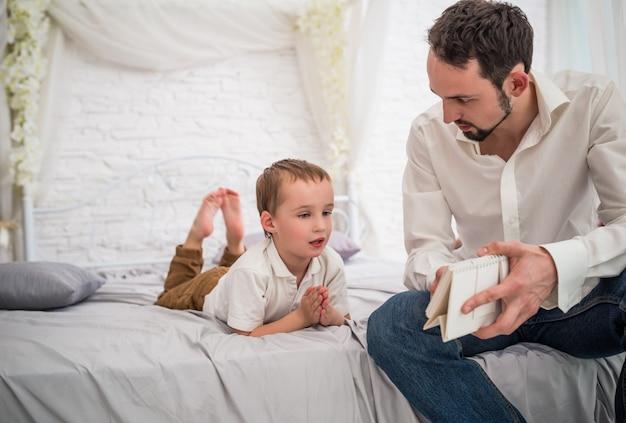 Młody ojciec rozmawia z ciekawym małym synkiem