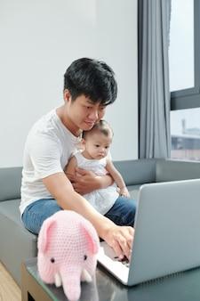 Młody ojciec siedzi na kanapie z córeczką na kolanach i pracuje na laptopie lub ogląda kreskówkę