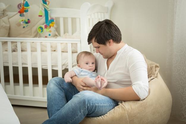 Młody ojciec siedzi z synkiem na rękach w sypialni