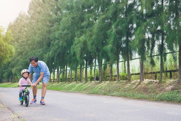 Młody ojciec spędza czas ze ślicznym małym azjatyckim dzieckiem 2-letnim chłopcem, tata i syn bawią się rowerem równowagi (biegać rowerem) na naturze, tata syn techniczny jeździ rowerem, koncepcja dnia ojca - filmowy wygląd