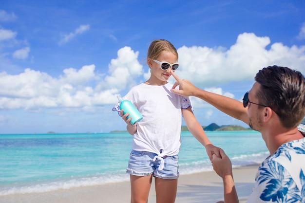 Młody ojciec stosuje krem do opalania dla córki