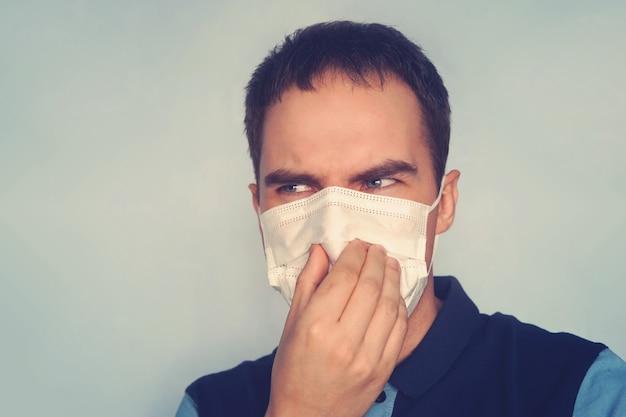 Młody ojciec trzyma brudne brudne pieluchy w palcach jednej ręki z maską gazową na białym tle. nieprzyjemny zapach śmierdzi. zła ekologia, zanieczyszczenie gazem