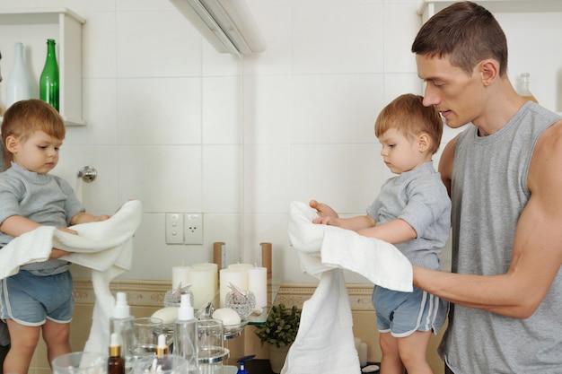 Młody ojciec uczy swojego małego synka wycierania rąk po porannym myciu w łazience