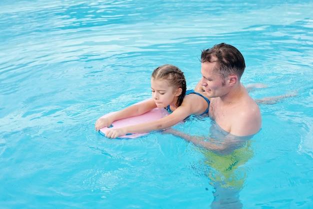 Młody ojciec wspierający małą córeczkę z deską do pływania, ucząc ją pływania w basenie we współczesnym centrum sportowym