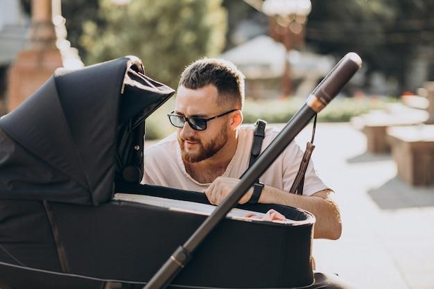 Młody ojciec wychodzi z dzieckiem w wózku dziecięcym
