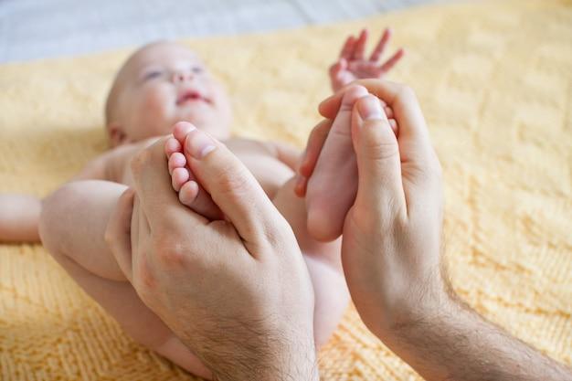 Młody ojciec wykonuje masaż dla szczęśliwego niemowlęcia na żółtej kratce z dzianiny