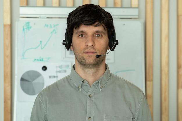 Młody operator call center stojący w swoim biurze z zestawem słuchawkowym patrzy w kamerę i uśmiecha się do obsługi linii pomocy call center
