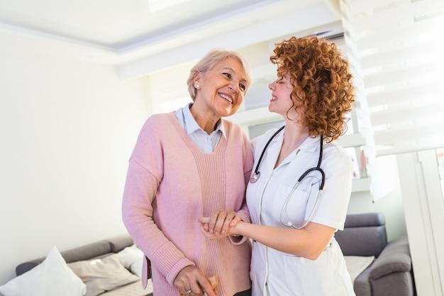 Młody opiekun wspiera starszej niepełnosprawnej kobiety z laską