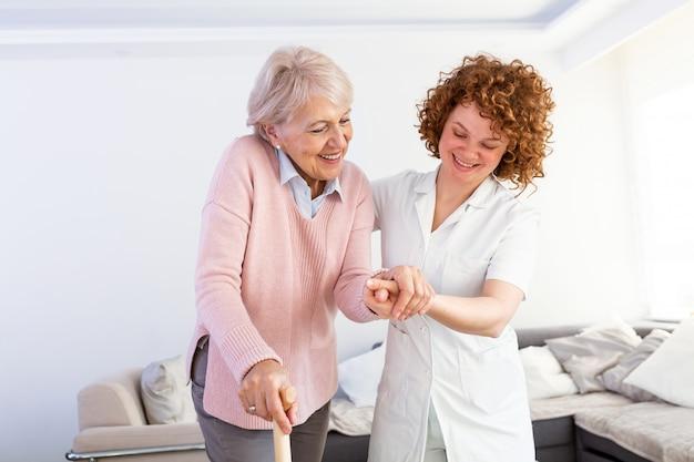 Młody opiekun wspiera starszej niepełnosprawnej kobiety z laską.