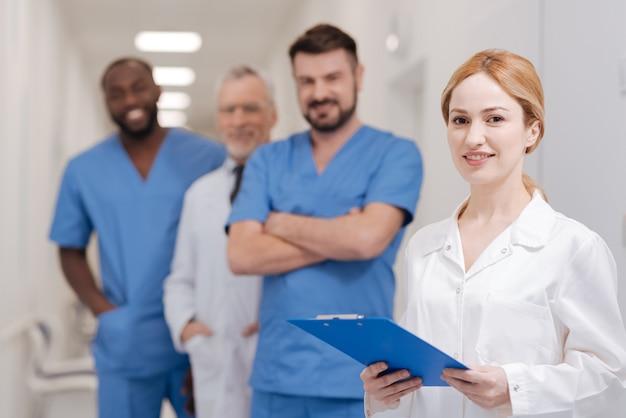 Młody, optymistyczny, charyzmatyczny lekarz, który wykonuje obowiązki w pracy i stoi w klinice z teczką w rękach, podczas gdy koledzy stoją