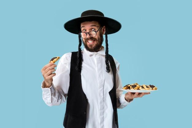 Młody ortodoksyjny żyd w czarnym kapeluszu z ciasteczkami hamantaschen na żydowskie święto purim