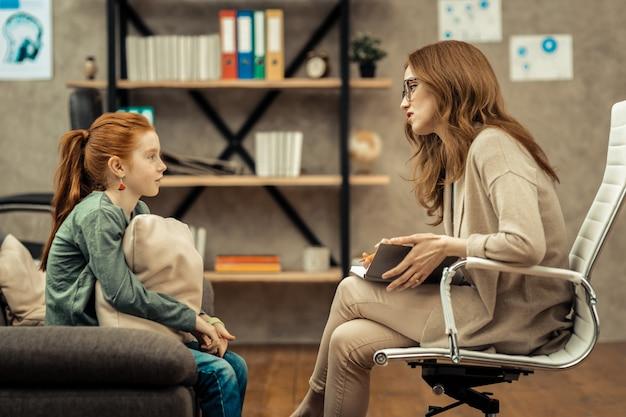 Młody pacjent. przyjemna profesjonalna terapeutka trzymająca swoje notatki podczas rozmowy z pacjentem