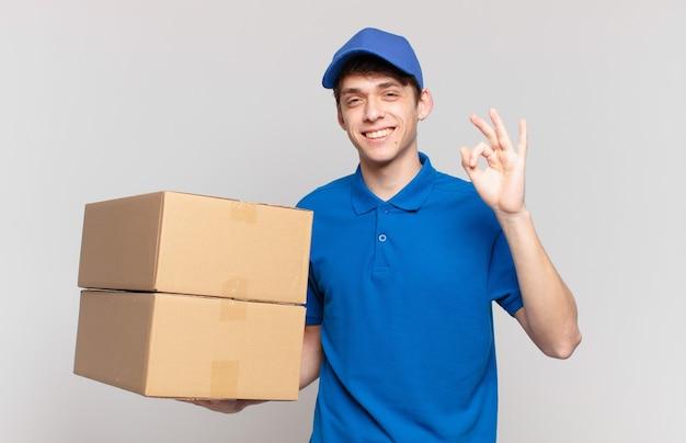 Młody pakiet dostarcza chłopca czującego się szczęśliwym, zrelaksowanym i usatysfakcjonowanym, okazując aprobatę z dobrym gestem, uśmiechnięty
