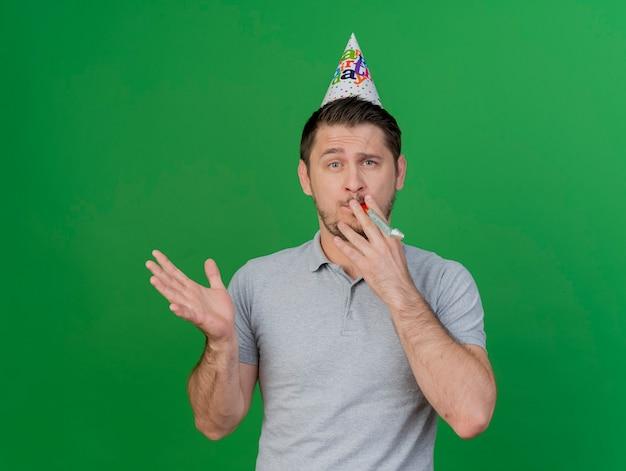 Młody partyjny facet ubrany w czapkę urodzinową, trzymając i dmuchając w gwizdek i rozprzestrzeniając rękę na białym tle na zielono