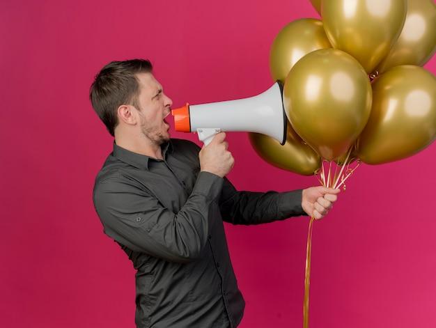 Młody partyjny facet ubrany w czarną koszulę, trzymając balony z boku, mówi przez głośnik na różowym tle