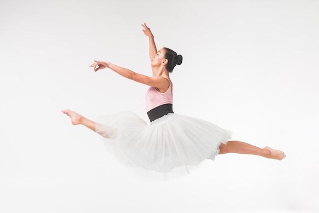 Młody pełen wdzięku żeński baletniczego tancerza doskakiwanie przeciw białemu tłu